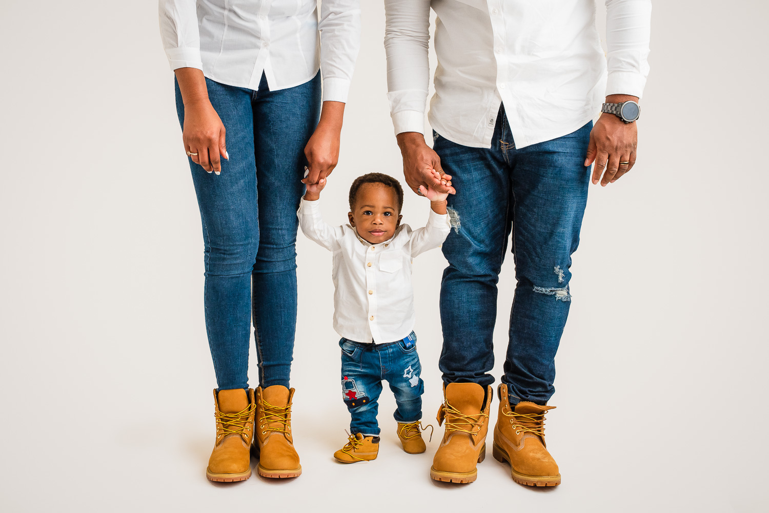 baby standing with parents